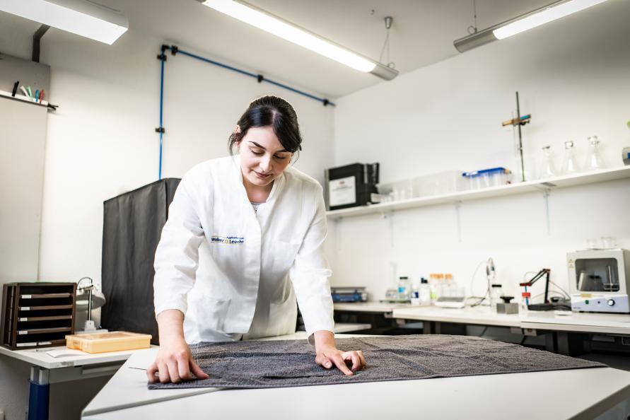 Katarina Röder, statlig sertifisert tekstillaboratorietekniker, måler hvor mye håndklærne har krympet etter at de ble vasket. Foto: Peter Jülich.