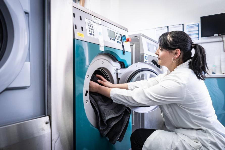 Her legger Katarina Röder, statlig sertifisert tekstillaboratorietekniker, et håndkle i en av laboratoriets vaskemaskiner. Fotograf: Peter Jülich.